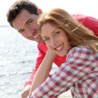 Stockfoto: Portrait of smiling couple standing by a lake