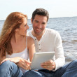 Couple using electronic tablet by a lake — Stock Photo #5695752