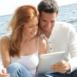 Couple using electronic tablet by a lake — ストック写真