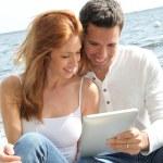 casal usando tablet eletrônico por um lago — Foto Stock