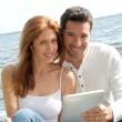 Couple using electronic tablet by a lake — Stock Photo