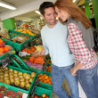 Couple at the supermarket doing grocery shopping — Stock Photo