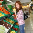 Woman at the grocery store buying fruits and vegetables - Stock Photo