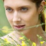 Portrait of beautiful woman in field of flowers — Stock Photo