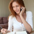 Self-employed woman at home talking on the phone — Stock Photo #5695923