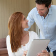 Couple at home using electronic tablet — Stock Photo #5695929