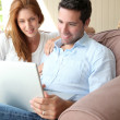Royalty-Free Stock Photo: Couple sitting in couch with laptop computer