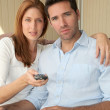 Couple sitting in sofa with tv remote control — Stock Photo