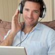 Handsome man listening to music on internet — Stock Photo