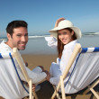 Couple sitting in longchairs at the beach — Stock Photo