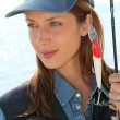 Portrait of woman with fishing rod - Stock Photo