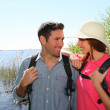 Happy couple hiking by a lake — Stock Photo