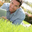 Man with electronic tablet in public park - Stock Photo