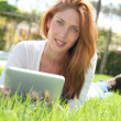 Beautiful woman websurfing with electronic tablet — ストック写真