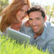 Portrat of couple laying down the grass with touchpad — Stock Photo