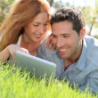 portrat de couple fixant l'herbe avec touchpad — Photo