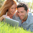 Portrat of couple laying down the grass with touchpad — ストック写真