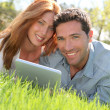 Portrat of couple laying down the grass with touchpad — Stockfoto #5696123