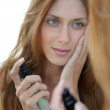 Beautiful woman putting foundation on her face — Stock Photo