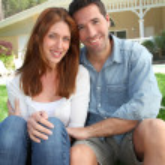 jovem casal sentado na frente de sua casa nova — Foto Stock