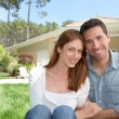 Young couple sitting in front of their new house — Stock Photo
