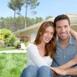 Young couple sitting in front of their new house — Foto Stock