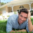 Smiling man laying down home garden — Stock Photo