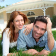 Happy couple laying down in their home garden — Stockfoto