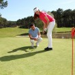 Foto Stock: Woman learning how to play golf