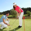 Woman learning how to play golf — Stockfoto
