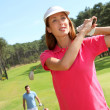 Couple playing golf on a sunny day - Stock Photo