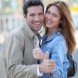 Happy couple with thumbs up in town — Stock Photo