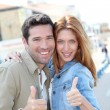 Portrait of smiling couple with thumbs up — Stock Photo