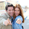 Portrait of happy couple pointing at camera — Stock Photo #5696297