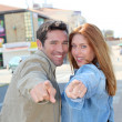 Portrait of happy couple pointing at camera — Stock Photo