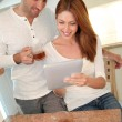 Royalty-Free Stock Photo: Young couple using electronic tablet in home kitchen