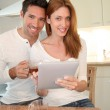 Young couple using electronic tablet in home kitchen — Stock Photo