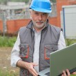 Stock Photo: Site manager with laptop computer checking construction