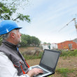 Site manager with laptop computer checking construction — Stock Photo