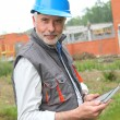 Site manager using electronic tablet — Stock Photo