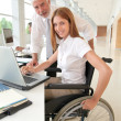 Royalty-Free Stock Photo: Woman in wheelchair with trainer in office