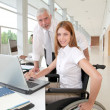 Woman in wheelchair with trainer in office - Stock Photo