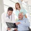 Medical team checking X-ray with patient — Stock Photo #5697201