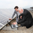 Businessmen checking solar panels running — Stock Photo