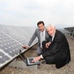 Businessmen checking solar panels running — Stock Photo #5697245