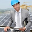 Businessman standing on solar panel installation — Foto de stock #5697279