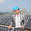 Businessman standing on solar panel installation — Stock fotografie #5697281