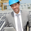 Foto Stock: Businessman standing on solar panel installation