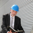 Site manager checking planning on computer — Stock Photo