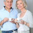 Senior couple taking coffee in kitchen — Stock Photo